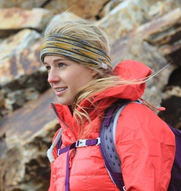 women in hiking attire looking forward with wind hitting her face