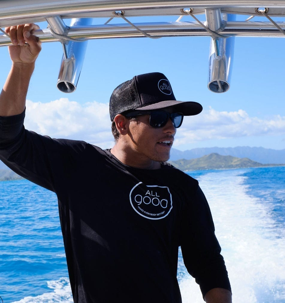 Man standing on a boat wearing All Good shirt and hat with ocean in the background