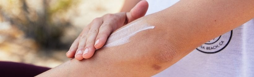 person rubbing lotion on their arm with elbow showing