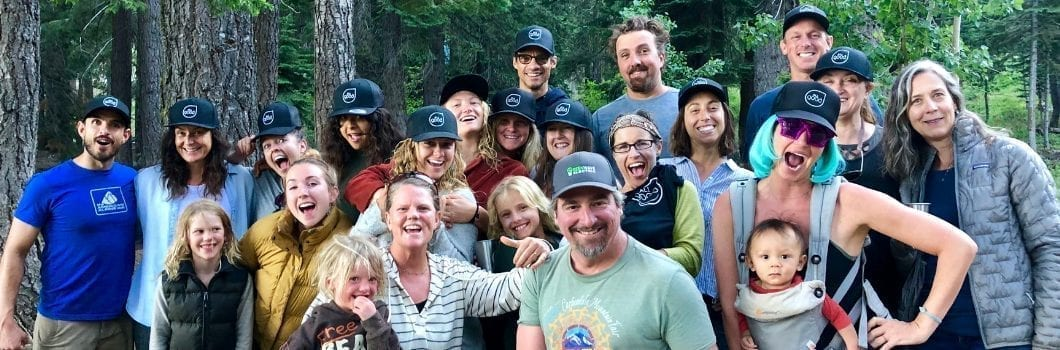 The All Good team standing in the woods smiling with All Good hats on.