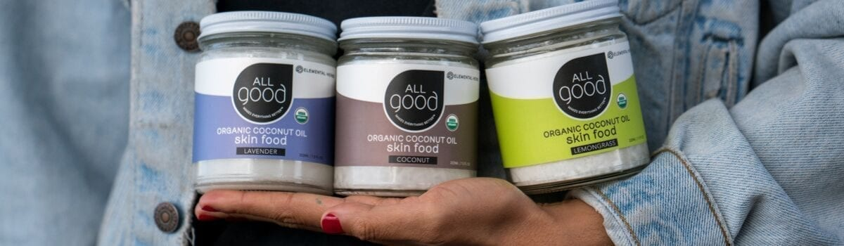 All Good organic lavender, lemongrass, and original coconut oil skin food held in front of woman's body