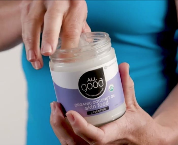woman dipping finger into All Good organic lavender coconut oil skin food