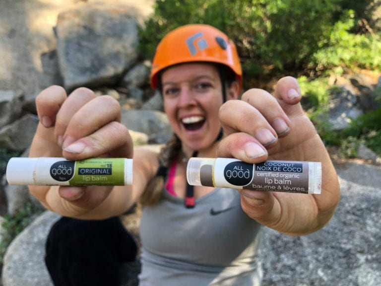 All Good team member holding up All Good Organic coconut and original SPF 15 lip balm at company retreat