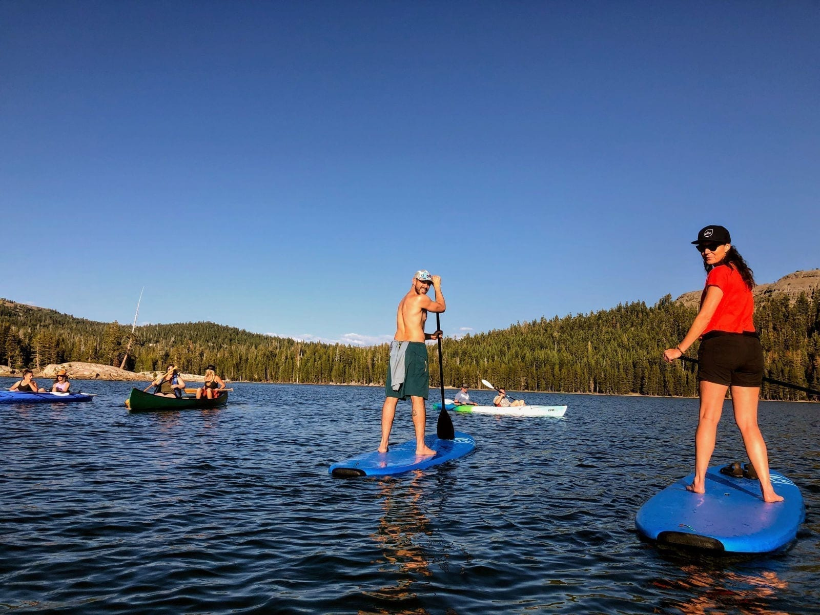 Man and woman on stand up paddle boards on the water with people in canoes and kayaks in the background