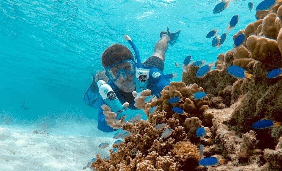 Man snorkeling by coral reef holding All Good sunscreen products