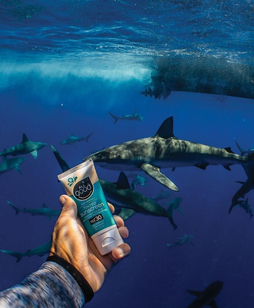 An arm holds up All Good Tinted Sunscreen Lotion underwater while sharks swim in the background.