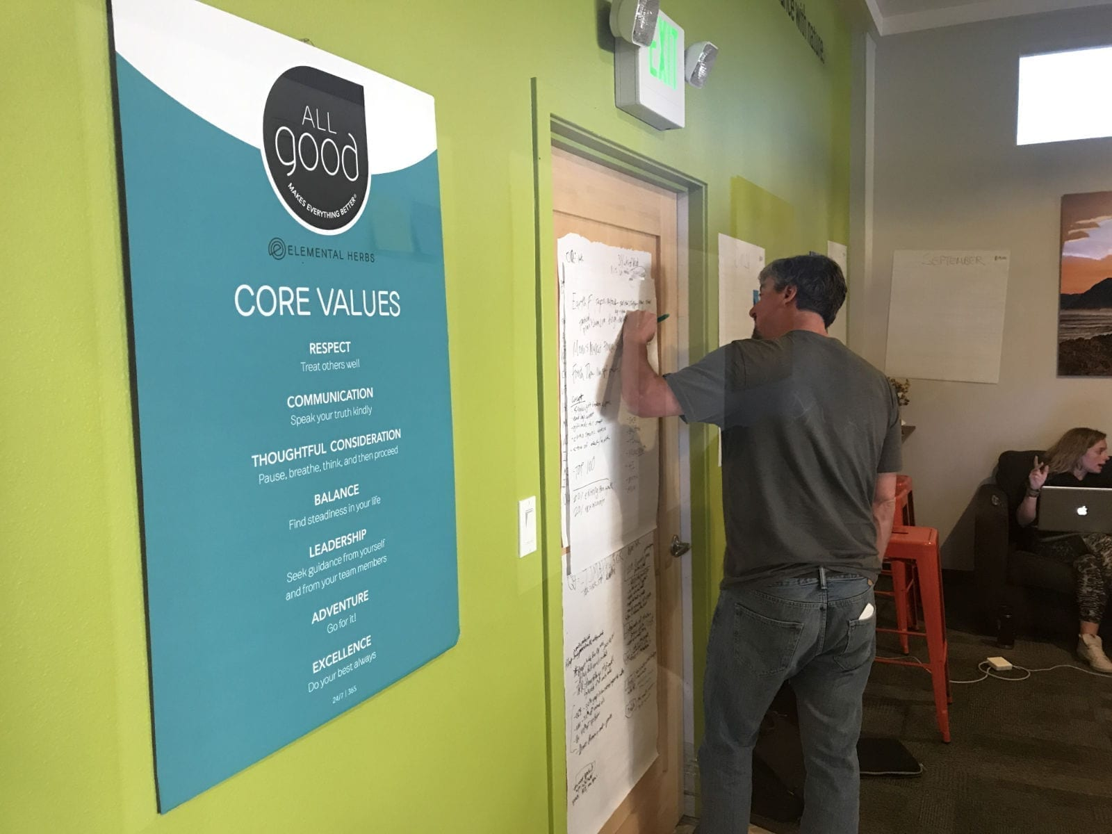 A man writes on paper with a poster of company values next to him on a bright green wall.