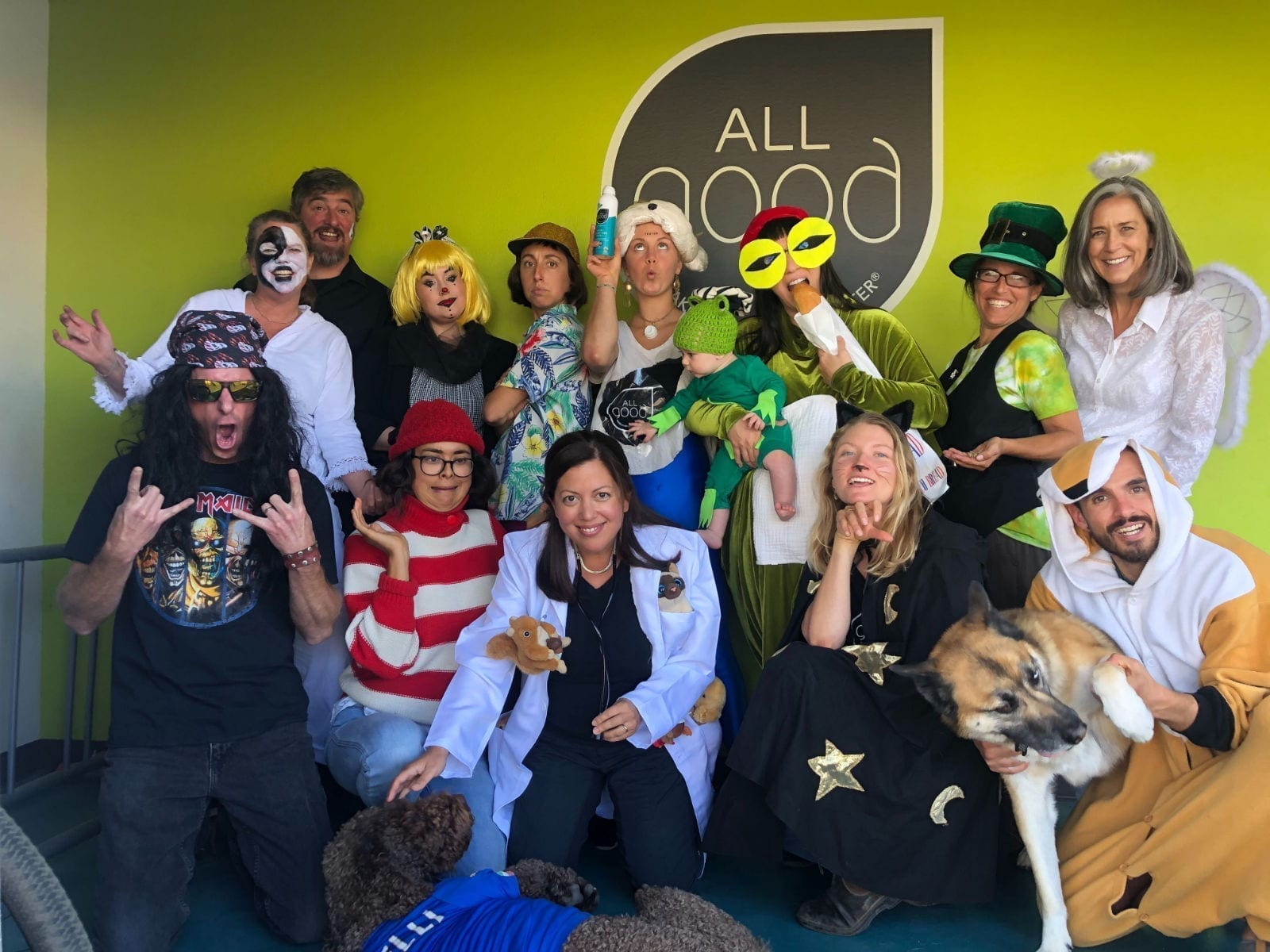 Members of the All Good team dressed in Halloween costumes strike a pose in front of the office logo.