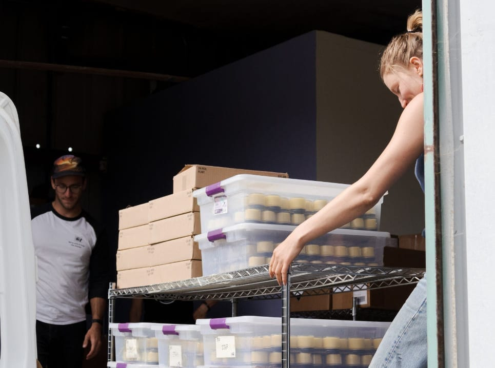 2 members of the All Good warehouse team are shown loading up the delivery van with All Good Goop.