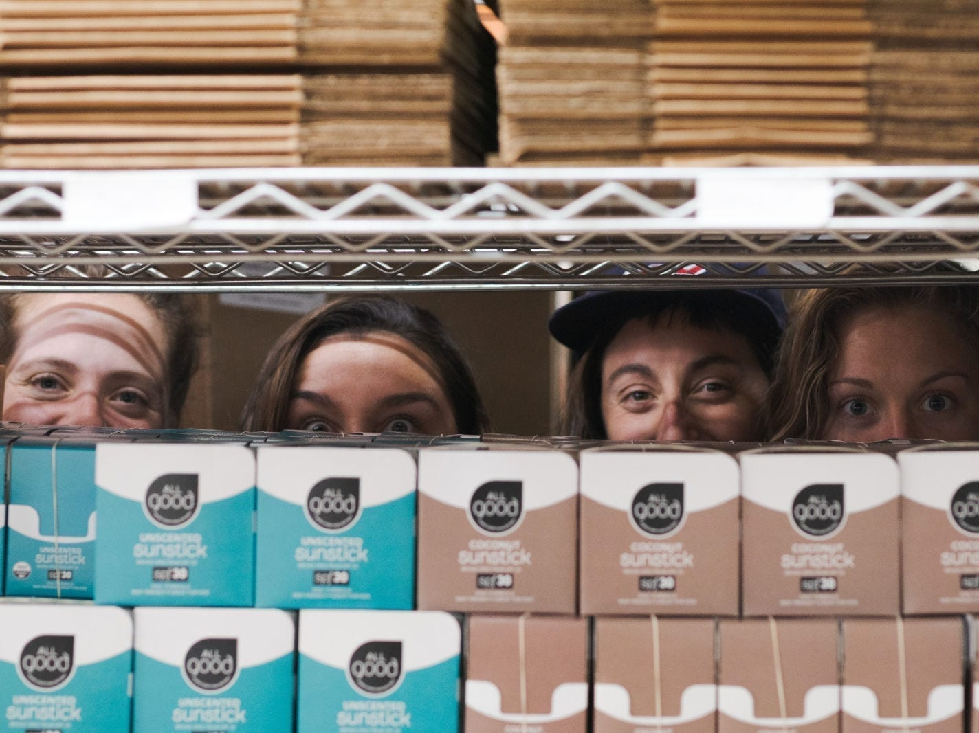 All Good team members peaking their eyes above shelf of mineral sunstick products