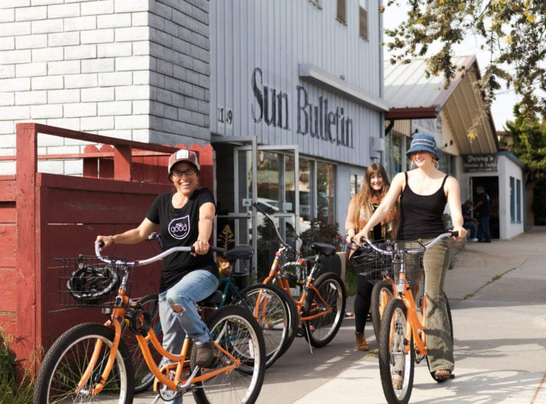 A photo of 3 women outside of the All Good headquarters riding orange bikes and smiling.