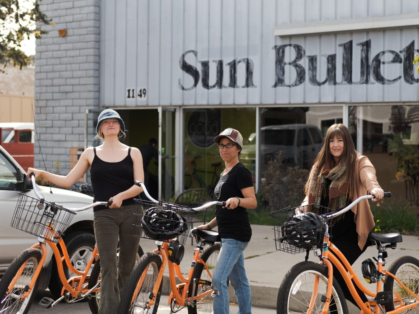 Members of the All Good team standing with matching beach cruiser bikes