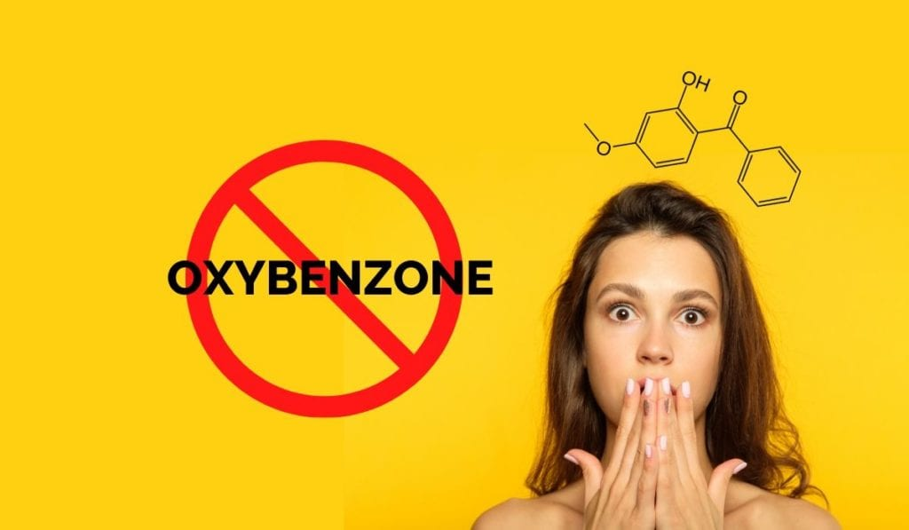Shocked woman on yellow background with prohibition label crossed through the word oxybenzone. Oxybenzone molecular structure shown.