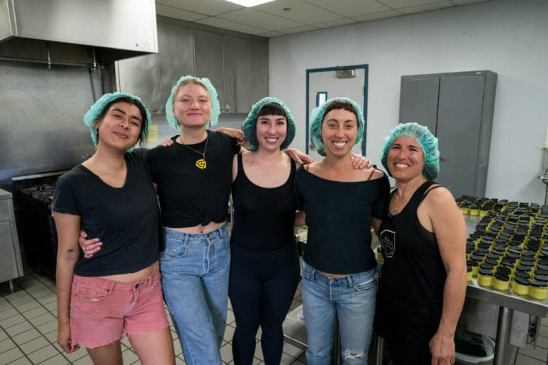 All Good goddesses smiling together with hair nets in All Good kitchen