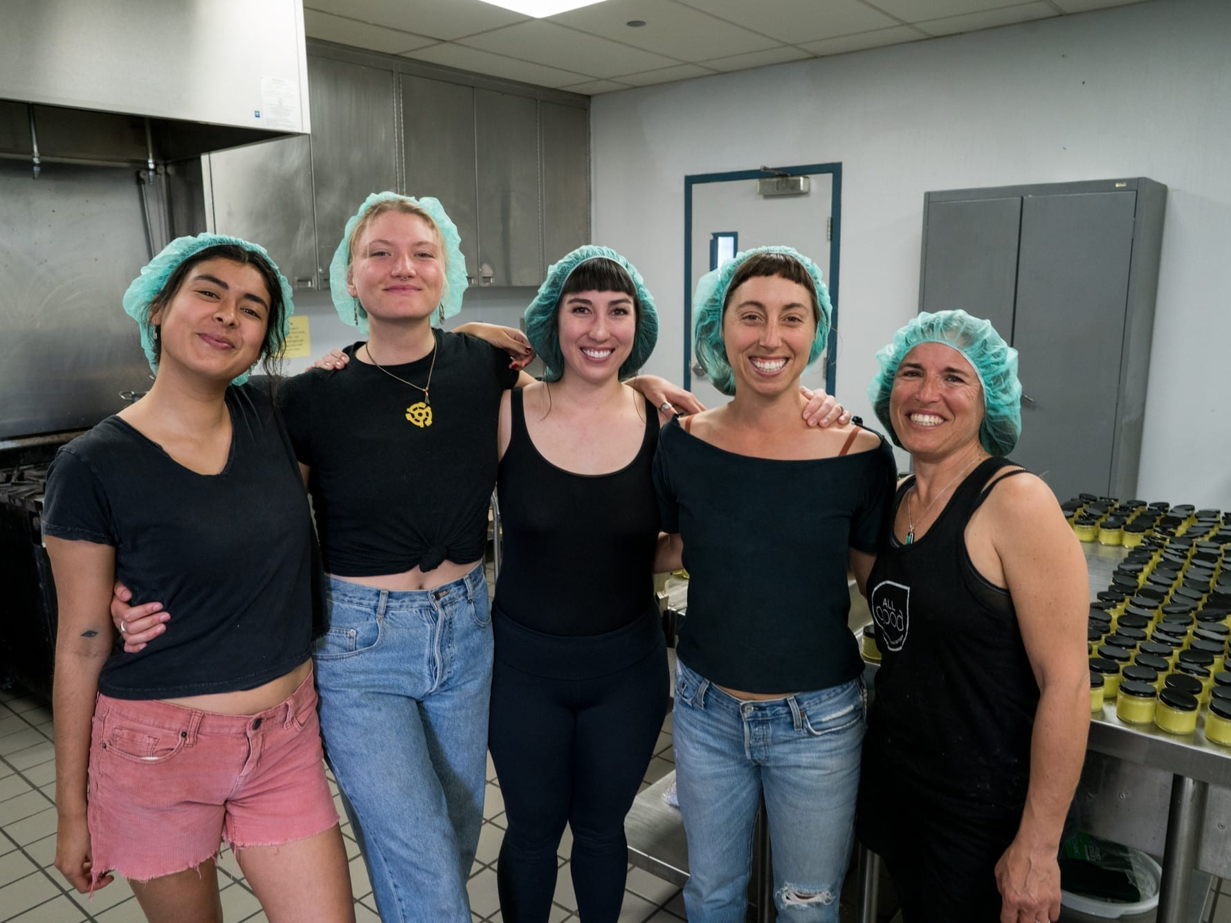 The All Good Goop Goddesses with hair nets and black t-shirts in the company kitchen stand side by side smiling.